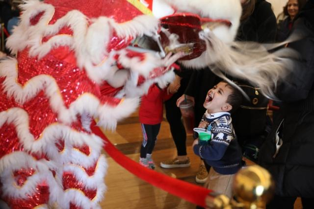 A boy watches a lion dance during the 2019 Lunar New Year Celebration at the John F. Kennedy Center for the Performing Arts in Washington DC on Feb 9, 2019. [Photo by Zhao Huanxin/chinadaily.com.cn]